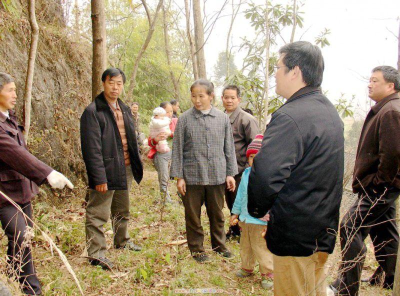 """图05:2015年12月,李木富的后人(左一),在""""红军洞""""前向秀山自治县副县长林光(右二)、民政局长(右一)等人,讲述当年李木富冒死掩护红军伤员的事迹。"""